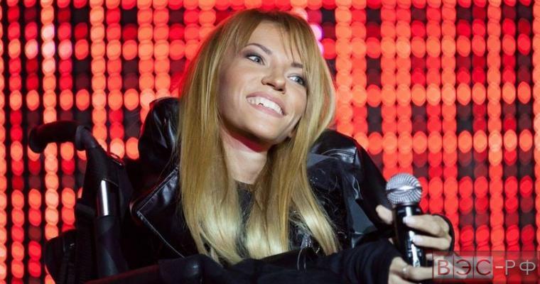 Юлия Самойлова улыбается с микрофоном в руках