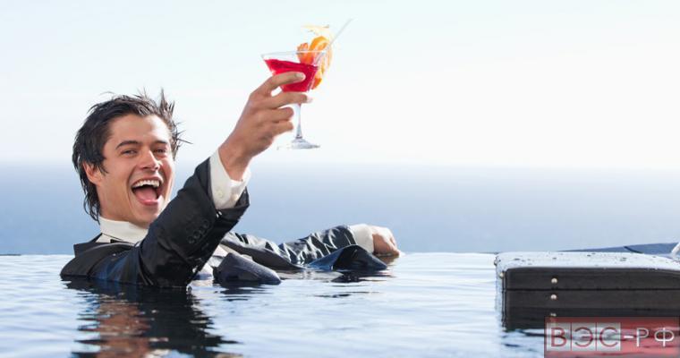 Мужчина в костюме сидит в бассейне и счастливо улыбается, попивая напиток