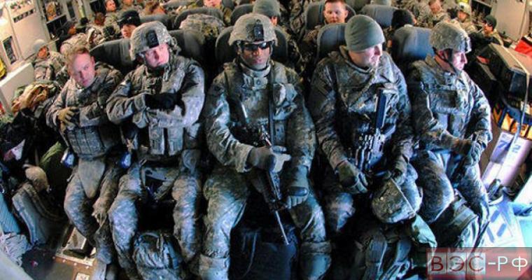 Военные США сидят в транспсорте, некоторые с оружием